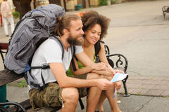 A couple of backpacker tourists sitting on a bench Royalty Free Stock Images