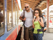 A couple of backpacker tourists waiting to board a train Stock Photos