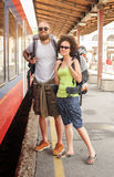A couple of backpacker tourists waiting to board a train Royalty Free Stock Photos