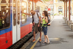 A couple of backpacker tourists waiting to board a train. At the railway station Royalty Free Stock Images