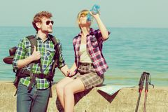 Couple backpacker tramping by seaside. Adventure, summer, tourism active lifestyle. Young couple backpacker tramping by seaside, girl drinking water from plastic Stock Photography