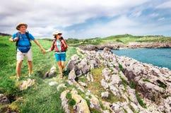 Couple backpacker travelers walk on ocean rocky coast. Asturias. Spain Stock Photos