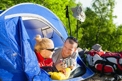 Couple backpackers camping in tent. Man and women hikers camping in summer nature. Happy young couple backpackers camping in tent, drinking coffee in morning royalty free stock image