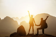 Couple backpackers hikers mountains sunset. Couple of backpackers or hikers stands with raised hands at mountain range background at sunset time. Space for text Stock Photography