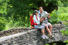 Couple of backpackers reading map in natural ambient Stock Photography