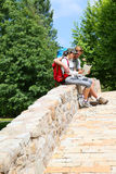 Couple of backpackers sitting on bridge and reading map Royalty Free Stock Photos