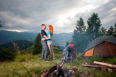 Couple backpackers standing near the campfire, tent, backpacks Stock Photo