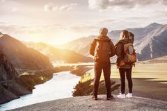 Couple backpackers travel mountains concept. Couple backpackers stands on background of mountain river and sunset. Travel and adventures concept with place for Stock Image