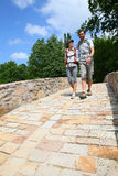 Couple of backpackers walking on bridge Stock Photos