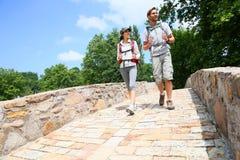 Couple of backpackers walking on bridge Royalty Free Stock Images