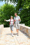 Couple of backpackers walking in peaceful place. Couple with backpack walking on stone bridge Stock Photos