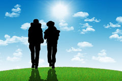 Couple of backpackers walking on a top of a hill towards the sun Stock Photos