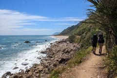 A Couple Backpacking Along the Heaphy Track in New Zealand. A couple backpacking near the beach on the Heaphy Track in New Zealand. The Heaphy Track is one of stock image