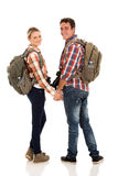 Couple with backpacks. Happy young couple with backpacks looking back on white background Royalty Free Stock Photos