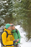 Couple with backpacks holding compass in snowy woods Royalty Free Stock Photos