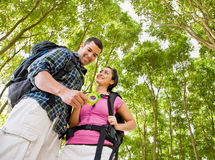 Couple in backpacks looking at compass Stock Photo