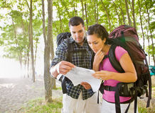 Couple in backpacks looking at map Royalty Free Stock Photos