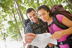 Couple in backpacks looking at map Stock Photography