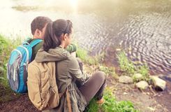 Couple with backpacks sitting on river bank. Travel, hiking, backpacking, tourism and people concept - couple with backpacks sitting on lake or river bank Stock Images