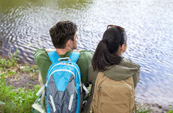 Couple with backpacks sitting on river bank Stock Image