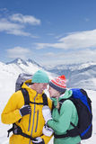Couple with backpacks smiling face to face on snowy mountain Stock Photo