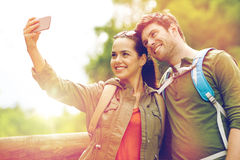 Couple with backpacks taking selfie by smartphone Royalty Free Stock Photos