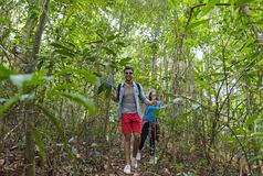 Couple With Backpacks Trekking On Forest Path, Young Man And Woman Holding Hands Walk On Hike Tourists stock photo
