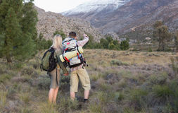 Couple with backpacks walking on forest landscape Royalty Free Stock Images