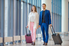 Couple with baggage in international airport. Man and woman going on landing. Young couple in international airport walking with her luggage Royalty Free Stock Photo