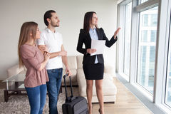 Couple with baggage rent apartment while travelling, meeting wit. Happy young couple travelers moving in new rented own apartment, standing by the window Royalty Free Stock Images