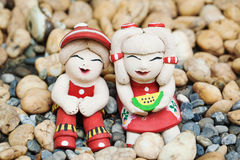 Couple of baked clay doll on polished stone Royalty Free Stock Photos
