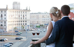 Couple on balcony with a glass of wine watching the city. Couple on balcony with a glass of wine watching the city Stock Photography