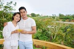 Couple on balcony. Hugging happy couple with orange juice standing on balcony Royalty Free Stock Image