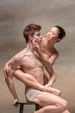 Couple of ballet dancers posing over gray background.  Stock Photos
