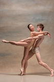 Couple of ballet dancers posing over gray background Royalty Free Stock Images
