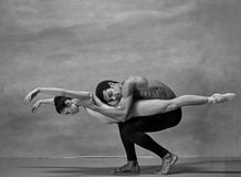 Couple of ballet dancers posing over gray background. Colorless image Stock Photography