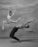Couple of ballet dancers posing over gray background. Colorless image Stock Image