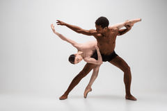 Couple of ballet dancers posing over gray background Royalty Free Stock Photo