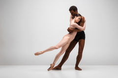 Couple of ballet dancers posing over gray background Stock Images