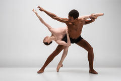Couple of ballet dancers posing over gray background Stock Photo