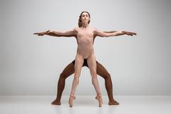 Couple of ballet dancers posing over gray background Stock Photos