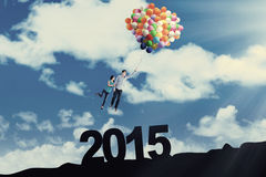 Couple with balloons above number 2015 Stock Photo
