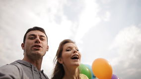 Couple with balloons fool around and shoot yourself in the phone. A couple in love in the park with colorful balloons stock video
