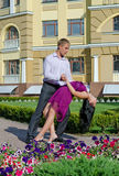 Couple ballroom dancing in a garden. Graceful young couple ballroom dancing in a formal garden in front of an old building in daylight Stock Photo