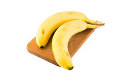 A couple of Bananas. On a cutting board, isolated on a white background Stock Photo