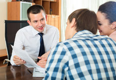 Couple and banking agent discussing Stock Image