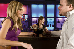 Couple at the bar. A couple sitting at bar with bar tender pouring a drink Royalty Free Stock Image