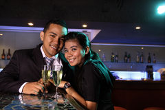 Couple at bar with champagne Stock Photos
