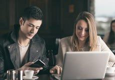 Couple at the bar using a laptop Stock Photos