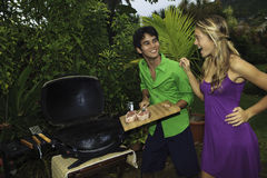 Couple barbecuing steaks Stock Photography